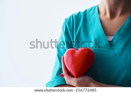 Female doctor holding heart over white background. - stock photo