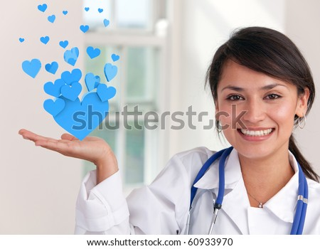 Female doctor holding hearts at the hospital and smiling - stock photo