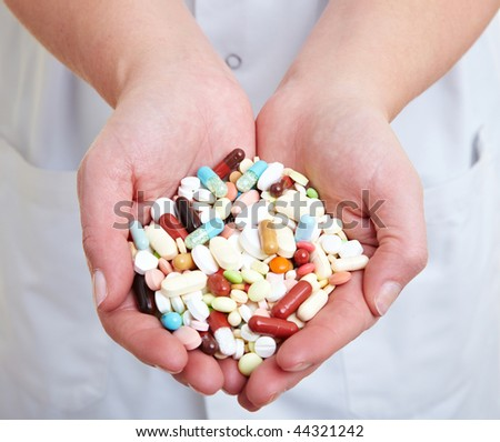 Female doctor holding many pills in her hands - stock photo
