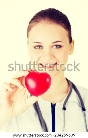 Female doctor holding red heart in hand. Isolated on white background - stock photo