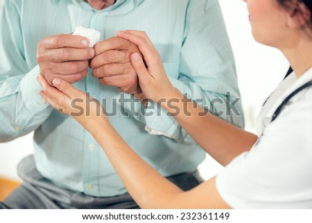Female doctor holding senior patients hands at medical office - stock photo