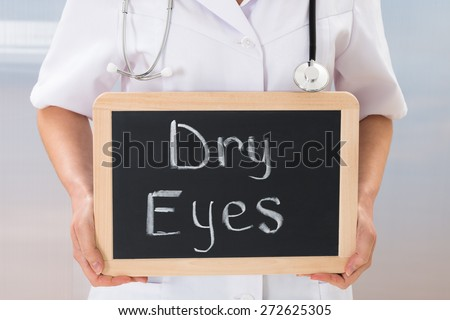 Female Doctor Holding Slate Chalkboard With The Text Dry Eyes - stock photo