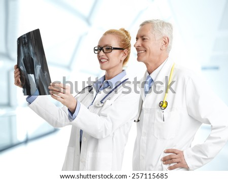 Female doctor holding x-ray image and consulting with male doctor at hospital.  - stock photo