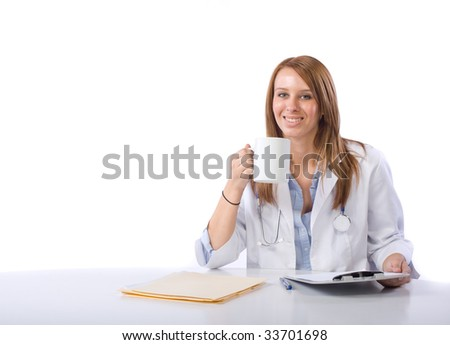 Female doctor in a modern office drinking coffee - stock photo