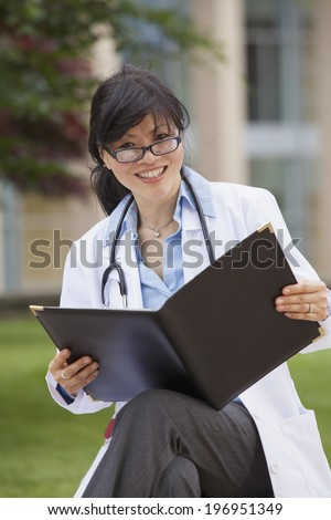 Female doctor in a white lab coat holding a binder of patient information - stock photo