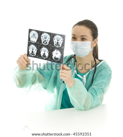 female doctor in green uniform and medical mask looking at tomography brain - stock photo