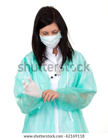 female doctor in medical mask pulling on surgical gloves