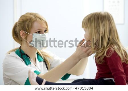 female doctor in medical mask study little girl - stock photo