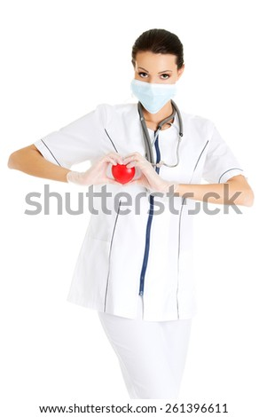 Female doctor in protecting mask holding heart model. - stock photo