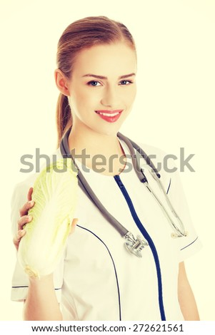 Female doctor in uniform holding cabbage - stock photo