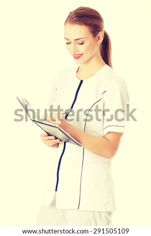 Female doctor in uniform writing results after research - stock photo