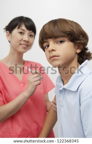 Female doctor injecting vaccine into boy's hand - stock photo