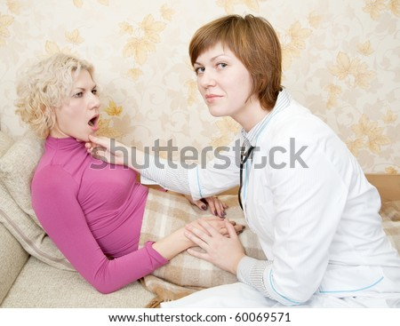 Female doctor loking to suffering girl on bed