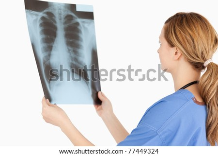 Female doctor looking at an X-ray on a white background