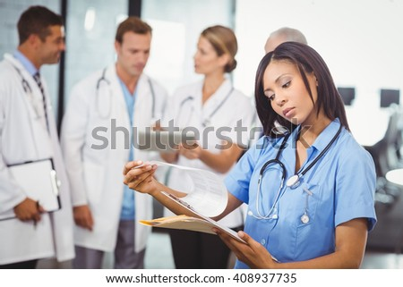 Female doctor looking at clipboard and colleagues standing and discussing in hospital - stock photo