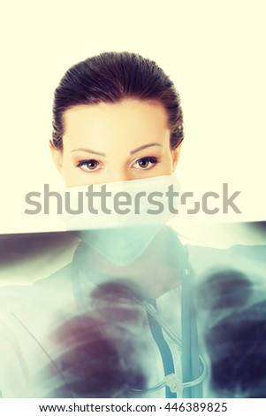 Female doctor looking at radiography photo - stock photo