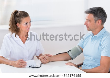 Female Doctor Measuring Blood Pressure Of Man In Hospital