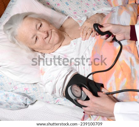 Female doctor measuring blood pressure of old woman - stock photo