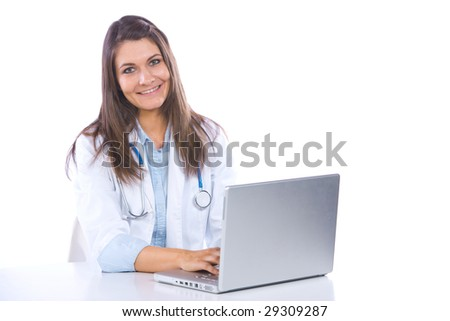 Female doctor on computer at desk isolated on white
