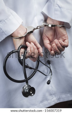 Female Doctor or Nurse In Handcuffs and Lab Coat Holding Stethoscope. - stock photo
