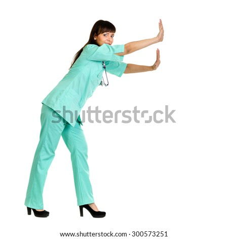 Female doctor or nurse pushing or leaning on wall. Isolated on white background - stock photo