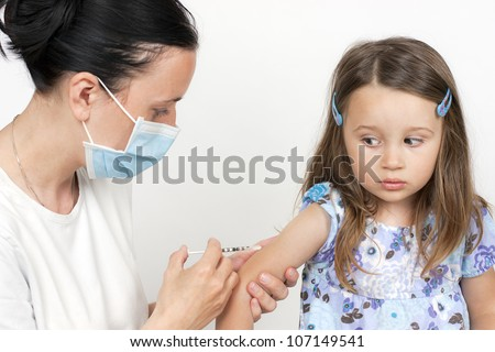 female doctor pediatrician with breathing mask over mouth giving child an intramuscular injection in arm - stock photo