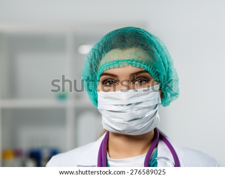 Female doctor's face wearing protective mask and green surgeon's cap closeup. Surgeon's eyes close up gazing intently in camera. Resuscitation concept. - stock photo