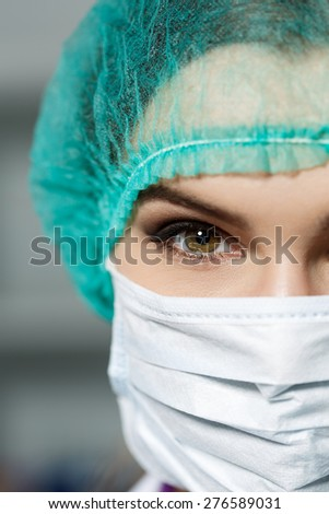Female doctor's face wearing protective mask and green surgeon's cap closeup. Surgeon's eyes close up gazing intently in camera. Resuscitation concept.