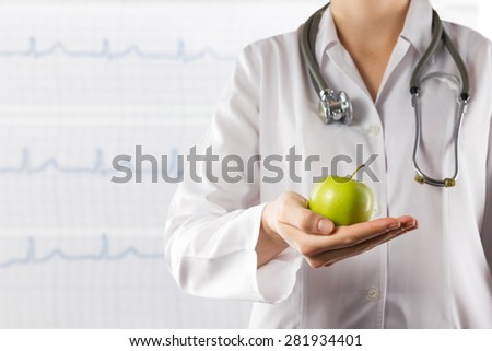 Female doctor's hand holding green apple. Close up shot on blurred medical background. Concept of Healthcare And Medicine. Copy space - stock photo