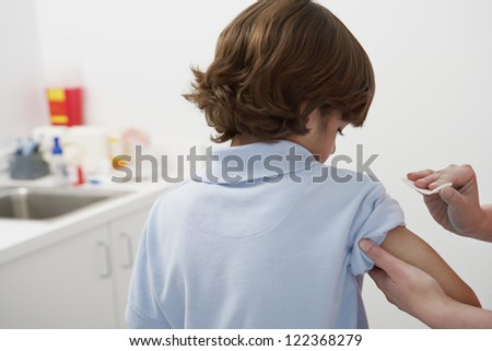 Female doctor's hand rubbing tissue paper before injection - stock photo