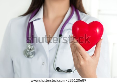 Female doctor's hands holding red heart in front of her chest. Doctor's hand closeup. Medical help, prophylaxis or insurance concept. - stock photo