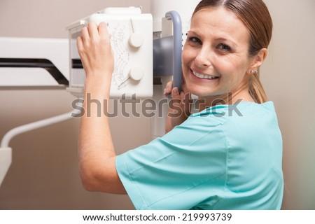 Female doctor setting up medical machine. - stock photo