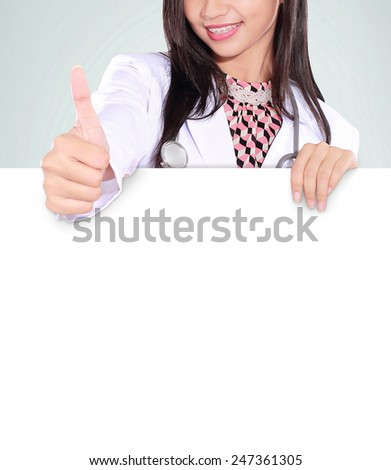 female doctor showing thumbs up and bring an empty board, isolated on green background - stock photo