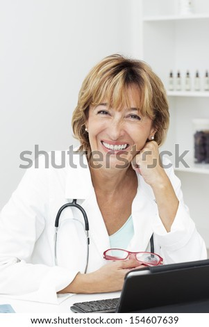 Female doctor sitting at the desk with hand on her chin and looking at camera. - stock photo