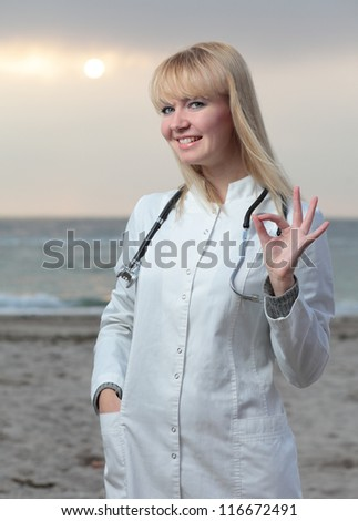 Female doctor smiling on the background of the sea. - stock photo