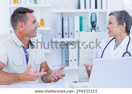 Female doctor speaking with her patient in medical office - stock photo