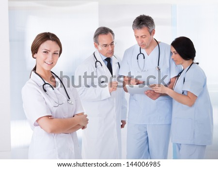 Female Doctor Standing In Front Of Team Using Digital Tablet - stock photo
