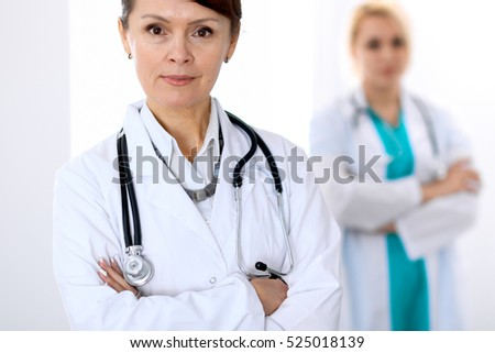 Female doctor standing with arms crossed in hospital. Medicine and health care concept.