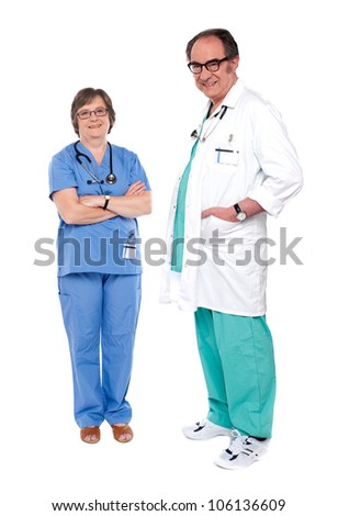 Female doctor standing with crossed arms while male doctor posing with hands in pocket - stock photo