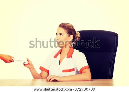 Female doctor take money from patient - stock photo