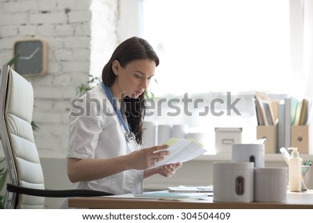 Female doctor taking notes during looking at patient medical tests at her office