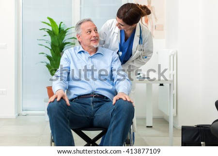Female doctor talking to a patient on a wheelchair - stock photo