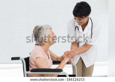 Female doctor talking to a senior patient in wheelchair at the hospital - stock photo