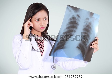 female doctor thinking and reading x-ray, isolated on green background - stock photo