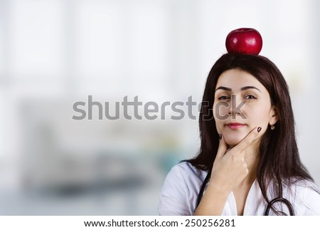 Female Doctor Thinking with an red apple on her head.Thoughtfully. - stock photo