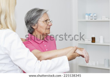 Female doctor touching a  shoulder to her senior women patient, giving  to her physical therapy.  - stock photo