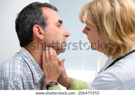 female doctor touching the throat of a patient in the office - stock photo
