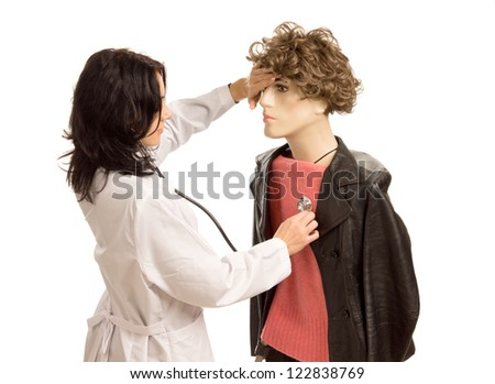 Female doctor treating a male mannequin holding a hand to its forehead and listening to the heart with a stethoscope, fun upper body studio portrait isolated on white