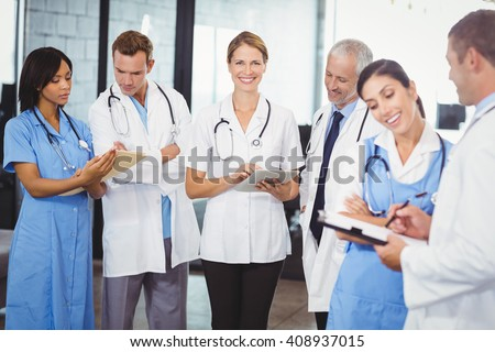 Female doctor using digital tablet and colleagues standing and discussing in hospital