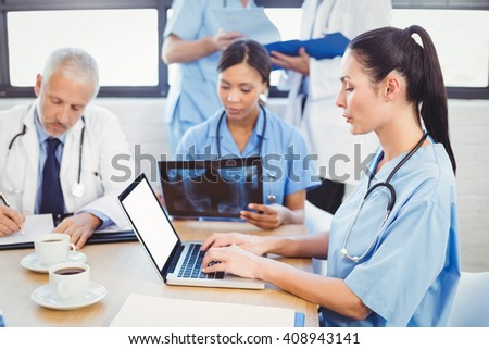 Female doctor using laptop in conference room and colleagues examining a x-ray in background - stock photo